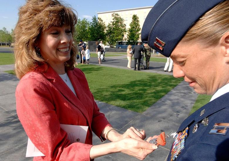 Susan Gamble, designer of the Air Force Combat Action Medal, looks at her work after one of the medals was pinned on Capt. Allison Black, 1st Special Operations Group, Hurlburt Field, Fla. The captain was one of the first six Airmen to receive the medal in a ceremony June 12 at the Air Force Memorial in Arlington, Va. (U.S. Air Force photo/Staff Sgt. Brian Ferguson)