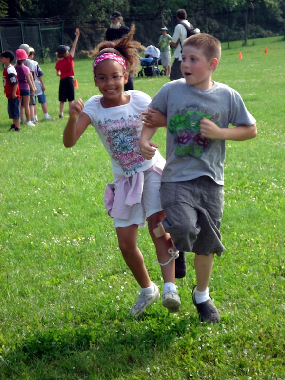 SPANGDAHLEM AIR BASE, GERMANY -- Bitburg Elementary School students Brooke Murray and Jacob Hitchcock run the three legged race event during a field day event. The students followed a volksmarch trail around the base with nine stations representing different local cities. At the stations children read information about the town and upcoming summer events. The students also participated in relay races, suitcase relay, tug-of- war and sack races. Brook is the daughter of Staff Sgt. Meghan Meyer, 52nd Maintenance Operations Squadron. Jacob is the son of Tech. Sgt. Matthew Hitchcok, 52nd Civil Engineering Squadron. (Photo by Dr. Sue Kerns)