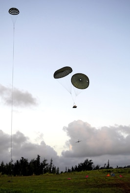 Practice airdrop bundles come in for a landing at the Kahuku Training Range in Hawaii Monday. The C-17's, from the 535th Airlift Squadron, Hickam Air Force Base, Hawaii are conducting their quarterly airdrop qualifications. (U.S. Air Force photo/ Tech. Sgt. Shane A. Cuomo)
