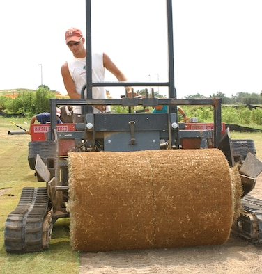 Equipment operator Brad Andrews from Southern Grass, West Point, rolls out sod on Hole 12 of Bay Breeze Golf Course June 6.  It's part of a $4.5 million project that's repairing damage from Hurricane Katrina and bringing the course up to U.S. Golf Association standards.  Bay Breeze is expected to reopen early this fall.  (U. S. Air Force photo by Kemberly Groue)