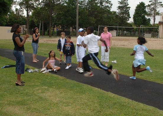 Volunteers and children join in on a relay race during a families of deployed members picnic. Events are held monthly by the Air Force Family Readiness Center here to provide the support needed for those families left behind during deployments.(U.S. Air Force photo by Senior Airman Veronica Pierce)