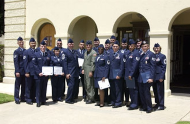 """The 452nd Air Mobility Wing Command Chief Agustin Huerta (left center), Commander Brig. Gen. James Melin (right center) and Chief of Education and Training Chief Master Sgt. Roberta Lewis (far right), celebrated a """"job well done"""" as 16 wing members received certificates of graduation from the Community College of the Air Force. The graduates were: Senior Master Sgt. John Thomas; Master Sgts Garold Cole, Jesse Hagen, Robert Healey, Francis Nesbitt and Lisa Turiano; Tech. Sgts Troy Castro, Robert Newton II, Raul Quintero, Sunny Saelee and Michael Stefanovich; Staff Sgts John Brown, Jr, Ryan Slanina, Aja Smith and Stanley St John; Senior Airman Matthew Carlton. (U.S. Air Force photo by Amy Abbott)"""