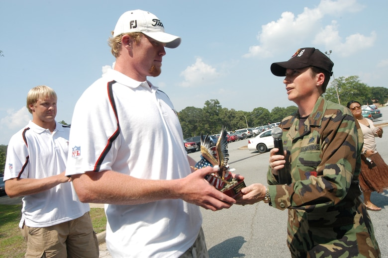 Boone Stutz, long snapper with the Atlanta Falcons, accepts an eagle from Col. Theresa Carter, 78th Air Base Wing commander at FalconFest Monday. U. S. Air Force photo by Sue Sapp