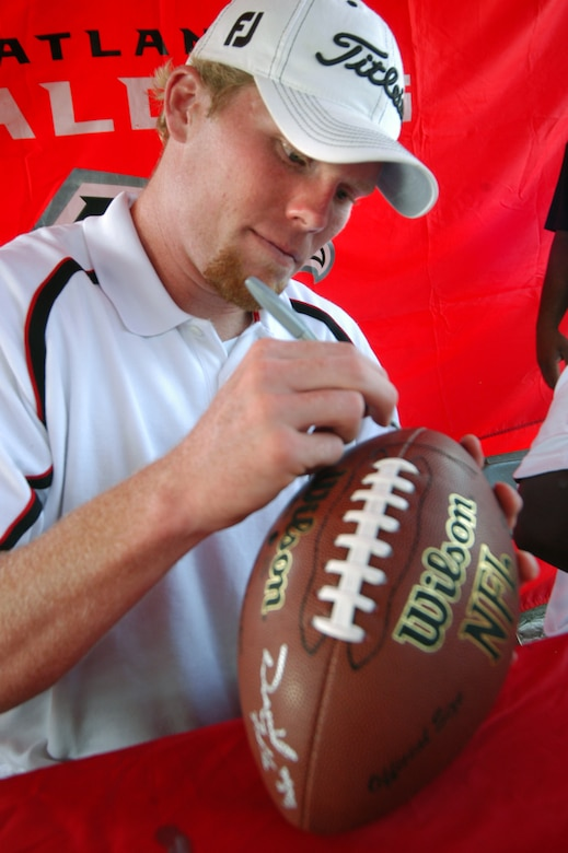 Boone Stutz, Atlanta Falcon long snapper, signs a football for a fan. U. S. Air Force photo by Sue Sapp
