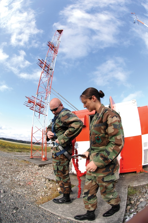 Staff Sergeant Jessica Wilhelm, right, assists Senior Airman Nicholas Higbee, adjust his harness on Tuesday May 22, 2007 prior to performing corrosion control on an antenna situated atop the Glideslope tower. SSgt Wilhelm and SrA Higbee are airfield systems maintenance technicians assigned to the 62nd Communications Sqaudron. (U.S. Air Force photo/Abner Guzman)(Released)