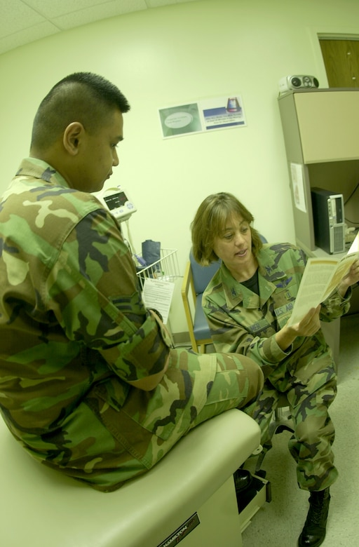 Dr. (Col.) Kathleen Elmer, 17th Medical Group chief of clinical services, reviews a brochure with Airman 1st Class Paolo Melendez, a member of the 17th Medical Operations Squadron Bioenvironmental Engineering Element. The base clinic handles approximately 200 medical appointments each day. (Photo by Airman 1st Class Luis Loza Gutierrez)