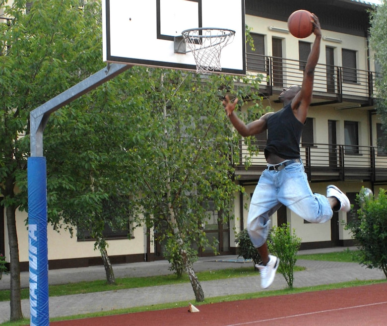 """SPANGDAHLEM AIR BASE, GERMANY -- Airman 1st Class Jerry """"Handles"""" Murrell, 52nd Security Forces Squadron, attempts to slam dunk a basketball June 7 at Spandahlem AB. Fitness is everyone's personal responsibility. (US Air Force photo/Airman 1st Class Stephanie Clark)"""