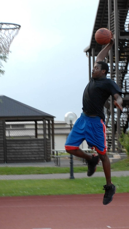 """SPANGDAHLEM AIR BASE, GERMANY -- Airman 1st Class Kristopher Davis, 606th Air Control Squadron, shoots some hoops in his free time June 7. Staying active outside of organized physical training keeps Airmen """"fit to fight."""" (US Air Force photo/Airman 1st Class Stephanie Clark)"""