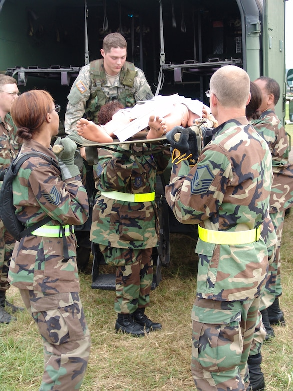 U.S. Army Specialist Aaron Tripp, 477th medical Company ground ambulance, Minnesota Army National Guard (top), assists members of the 706th Provisional contingency aeromedical support facility, in unloading patients from the Army's combat support hospital at Fort Gordon, Ga., during Golden Medic 2007.