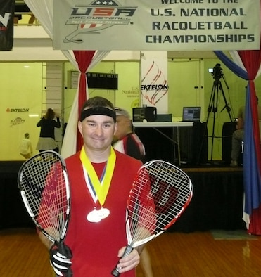 "Tech. Sgt. Shaun Stone, 961st Airborne Air Control Squadron E-3 airborne communications systems operator, poses with his medals at the U.S. National Singles Racquetball Championships held in Houston, Texas, recently. Sergeant Stone earned the silver medal in the ""B"" skill division and the gold in the over 35 ""A"" skill division."