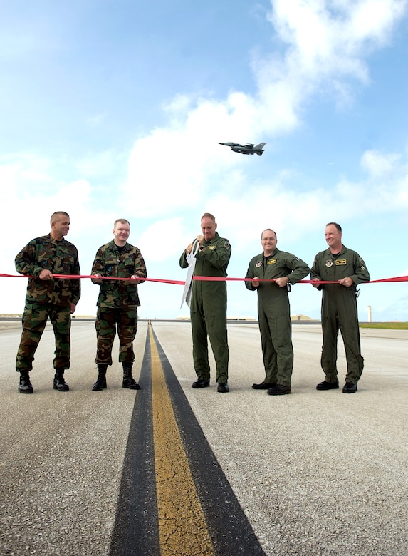 Brig. Gen. Doug Owens, 36th Wing commander, flies the first operational F-16 sortie over Andersen's newly re-opened north runway.  Lt. Col Pete Ridilla, 36th Civil Engineer Squadron commander; Col. Mark Talley, 36th Mission Support Group commander; Col. Joel Westa, 36th Wing vice commander; Col. Damian McCarthy, 36th Operations Group commander; and Lt. Col. Dave Hornyak, 36th Operations Support Squadron commander cut the ribbon marking the official opening of the runway following nearly two years of construction aimed at improving mission capability and safety.
