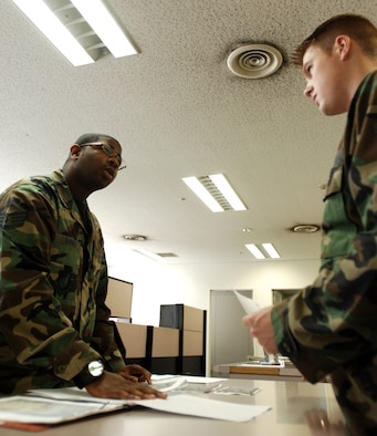 Staff Sgt. Fernando Barnes, 374th Communications Squadron deployment manager, reviews Airman Garret Cole's, 374 CS, folder and records during the Unit Self Inspection week. Unit's are encouraged to begin a checklist on unit documentation for preparation of the Unit Compliance Inspection in January. (U.S. Air Force photo by Airman 1st Class Laszlo Babocsi)