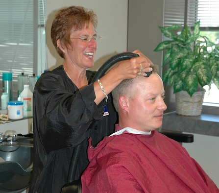 SCHRIEVER AIR FORCE BASE, Colo. -- Dawn Guggenbiller converses with Randy Rose, a contractor with the Missile Defense Integration and Operations Center, as she cuts his hair June 18. Ms. Guggenbiller is the barber at Schriever's Barber Shop, located on the second floor of the DeKok Building here. (U.S. Air Force photo/Lorna Gutierrez)