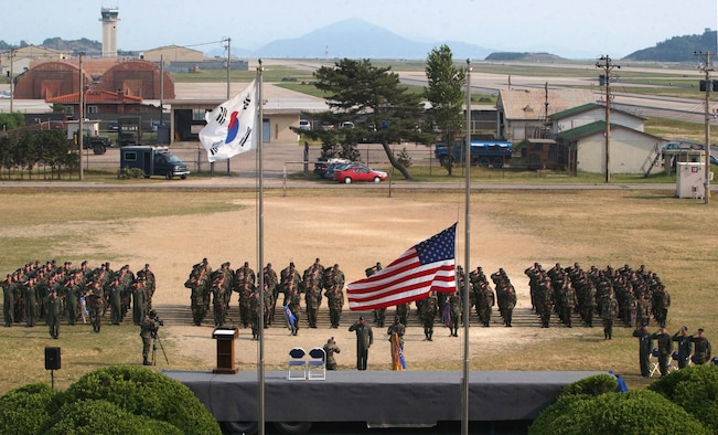 "KUNSAN AIR BASE, Republic of Korea -- Airmen from the 8th Fighter Wing salute for retreat during the wing's commemoration event June 19.  The memorial service honored the memory of ""Wolf 1"", Brig. Gen. Robin Olds, who recently passed away.  (U.S. Air Force Photo/Senior Airman Steven R. Doty)"