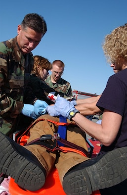 EIELSON AIR FORCE BASE, Alaska --  354th Medical Group members help in the aid of an injured bystander June 19 here. Eielson held an emergency management exercise to help in the readiness and response in case of unforeseen events, members of the medical group attend to those who are injured and to make sure they get the attention and care they need.   (U.S. Air Force photo by Airman 1st Class Christopher Griffin)
