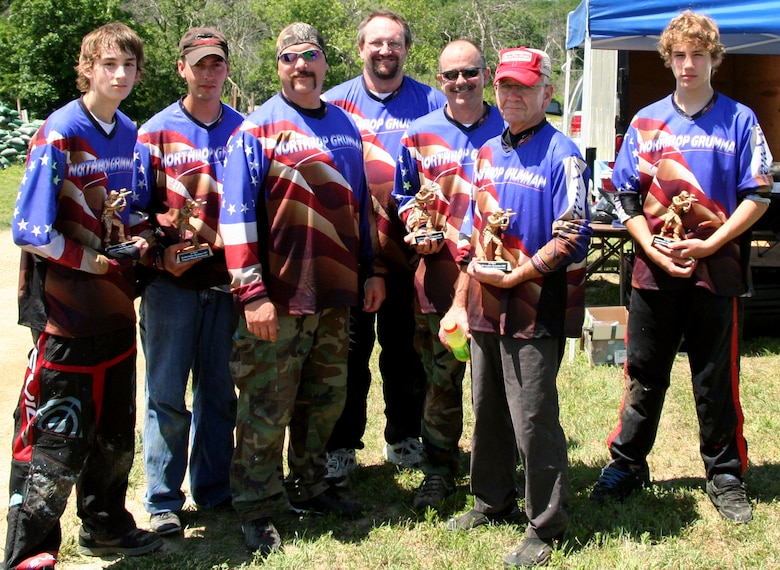 The Northrop-Grumman paintball team, 'The Company', stands proud as the winners of the Area 509 grand opening paintball tournament June 9. The Company won the tournament 4-1 in a best of seven competition against the 'Shadow Brigade.' They are: (from left to right) Robbie Gillaspie, Ethan Souder, Jeff Blake, Scott Gillaspie, Mark Andrews, Ken Gallagher and Mike Taylor. (U.S. Air Force photo/Staff Sgt. Jason Barebo)