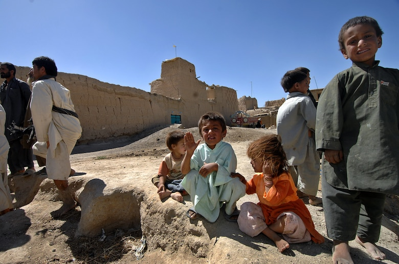 A group of children awaits a delivery of humanitarian supplies being delivered to the village of Qal' ehey Yuzbashi in Afghanistan. Lt. Gen. John Bradley, the Air Force Reserve Command commander and chief, was delivering the supplies to the village located near Bagram Air Base. The supplies, destined for refugee camps, orphanages and hospitals throughout Southwest Asia, are part of the 9,000 pounds collected by General Bradley's wife, Mrs. Jan Bradley. General Bradley is visiting Airmen throughout Southwest Asia to thank them for their service supporting the war on terrorism. (U.S. Air Force photo/Tech Sgt. Rick Sforza)
