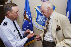 Air Force Maj. Gen. Robert L. Smollen, Air Force District of Washington commander, presents retired Col. Eugene P. Deatrick with his personal coin for his service in the Air Force. Deatrick was an Air Force pilot during the Vietnam conflict. While on assignment in Laos in 1966, Deatrick and his wing man discovered a SOS distress signal from downed Navy pilot, Dieter Dingler, and called for a rescue helicopter to pick him up. (U.S. Air Force photo by Bobby Jones)