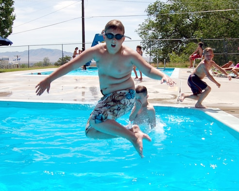June 21 is the first official day of summer, although the temperatures have already reached the high 90s. Hill Air Force Base kids have taken advantage of the warm weather, such as Tristan Pendley, 11, who jumps into one of the base swimming pools. (U.S. Air Force Photo by Beth Young)