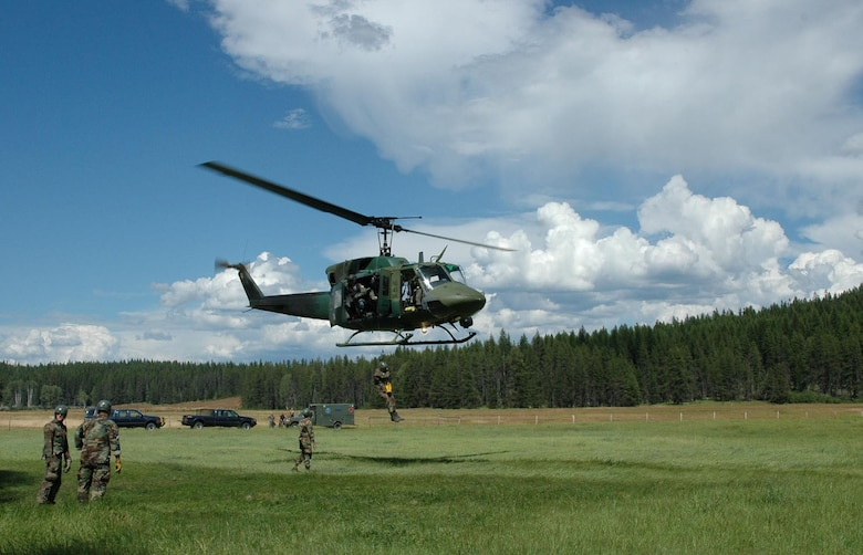 """A UH-1N """"Huey"""" hoists a Survival, Evasion, Resistance, Escape Specialist Training student at a landing zone north of Fairchild Air Force Base, Wash.  (U.S. Air Force photo by Tech. Sgt. Michael Darvis)"""