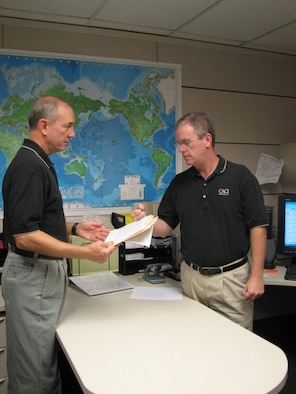 Ed Salisbury, task lead, executive airlift support and operational support airlift, 613th Air and Space Operations Center Air Mobility Division, discusses an upcoming executive airlift mission with Jeff Frye, primary Air Force executive airlift support planner. Both are CACI International, Inc., contract employees.  CACI has provided Pacific Air Force's mobility aircraft planning and dispatch functions for six years, but this is the first time a civilian contractor will perform these services for Commander, Pacific Fleet's Executive Transport Detachment. (USAF Photo by Capt. Yvonne Levardi.)