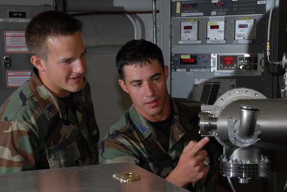 1st Lt. Ryan Hawley and Air Force Academy Cadet Greg Guy observe the critical pressure changes in AEDC's small vacuum research chamber. (Photo by Rick Goodfriend)