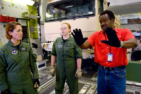 Howard Thagard, a loadmaster instructor with the C-17 Globemaster III aircrew training system instructs loadmaster students Airmen 1st Class Kelsey Gainer (left) and Jessica McLeroy in an $18 million cargo compartment trainer at Altus Air Force Base, Okla. Inside the simulated C-17 cargo compartment students get to try their hand at a variety of loads, to include pallets, vehicles, helicopters, heavy equipment and aeromedical set-ups. (U.S. Air Force photo/Tech. Sgt. Matt Hannen)