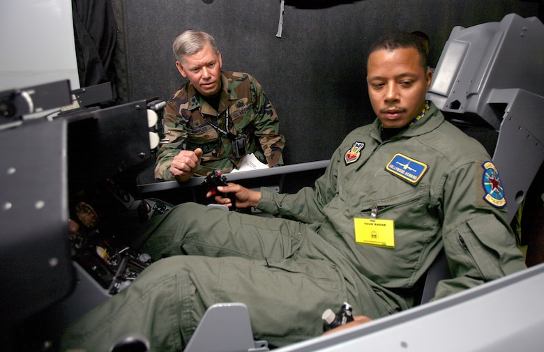 "Lt. Col. David Coppler instructs actor Terrence Howard on the controls of an F-16 Fighting Falcon simulator at Edwards Air Force Base, Calif., to help prepare Howard for his role in the movie, ""Iron Man."" Movie director Jon Favreau and his crew spent three days filming at Edwards AFB. Colonel Coppler is the 772nd Test Squadron commander. (U.S. Air Force photo/Jet Fabara)"
