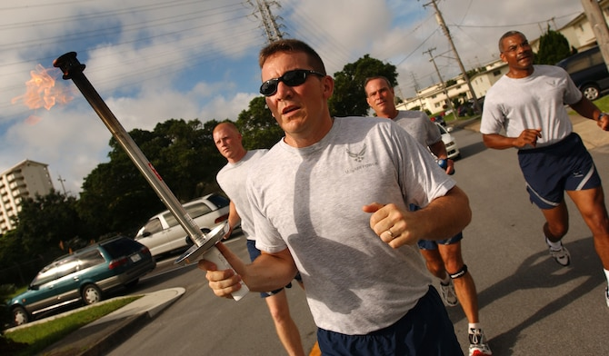 Tech. Sgt. Matt Howard, 18th Security Forces Squadron, leads a four-man team as they run from Gate 2 to Bldg. 705 before starting the Law Enforcement Torch Run at Kadena Air Base, Japan. Army, Navy, and Marines joined the run from Bldg. 72 to the Risner Gym June 16. The Torch Run is affiliated with Special Olympics nation wide and was adopted at Kadena to promote awareness for the annual event here.  (U.S. Air Force photo by Staff Sgt. Reynaldo Ramon)