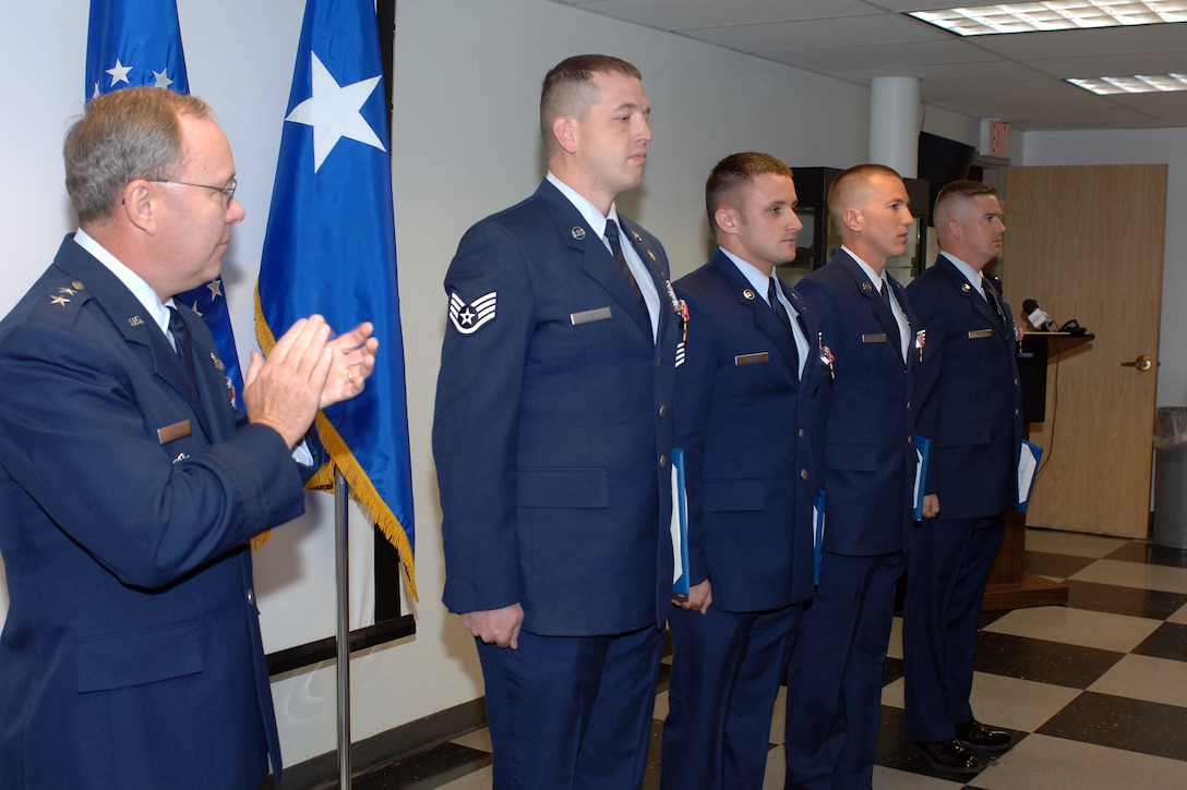 Maj. Gen. Kevin J. Sullivan, Ogden Air Logistics Center commander, presents Staff Sgts. Bradley Kline, Evan Knight, Steven Overstreet and William White. The Airmen, from the 775th Civil Engineer Squadron, Explosive Ordnance Disposal Flight, were presented the award for their efforts in the Global War on Terror (U.S. Air Force photo by Alex P. Llloyd)