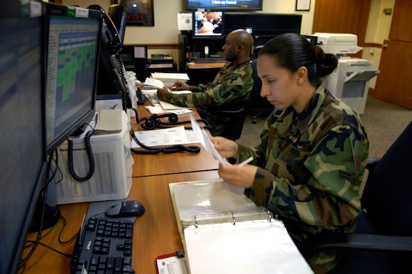Airman 1st Class Brenda Davis and Staff Sgt. Lynn Brown work at their control consoles inside the command post June 8 at Hickam Air Force Base, Hawaii. The Airmen are emergency actions controllers from the 15th Airlift Wing. (U.S. Air Force photo/Tech. Sgt. Shane A. Cuomo)