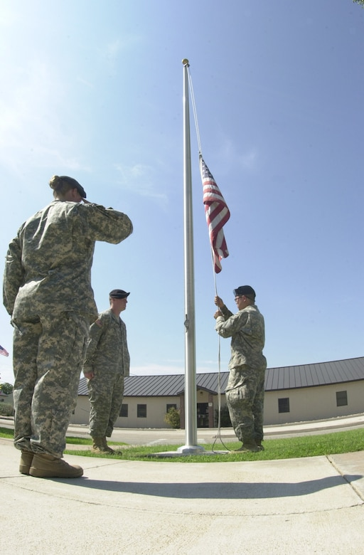 (From left to right) Sgt. 1st Class Susanne Watts salutes while Pfc. Kevin Bell and Spc. Hung Zhang ceremoniously lower the American flag which flies in front of the Vance Nolan Building, headquarters to the 344th Military Intelligence Battalion. The 344th retires the colors everyday during retreat, including weekends. The retreat ceremony serves a twofold purpose. It signals the end of the official duty day and serves as a ceremony for paying respect to the flag. 