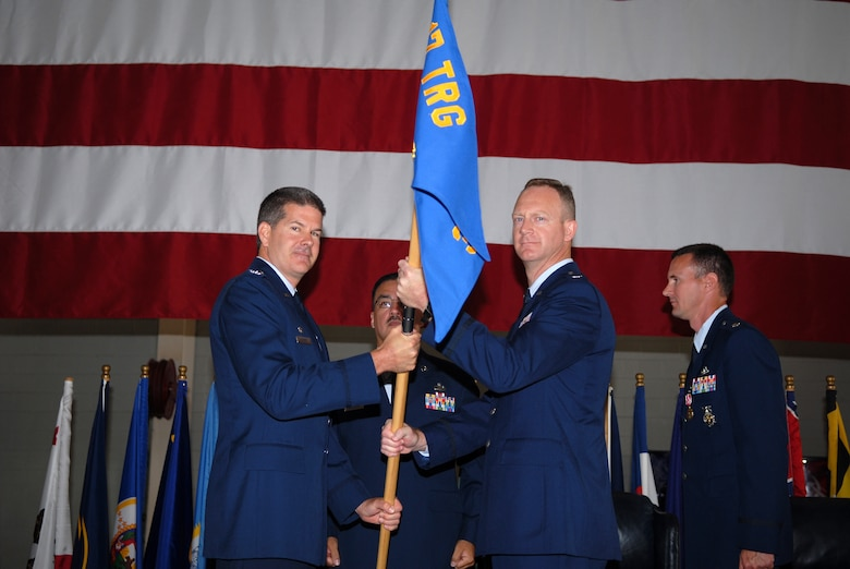 Col. D. Scott George, 17th Training Group commander, passes the 312th Training Squadron guidon to Lt. Col. Shawn Moore during a change-of-command ceremony held Tuesday at the Louis F. Garland Fire Academy. Lt. Col. Moore replaces Lt. Col. Mark Zimmerhanzel. (U.S. Air Force photo by Tech. Sgt. Gina O'Bryan)