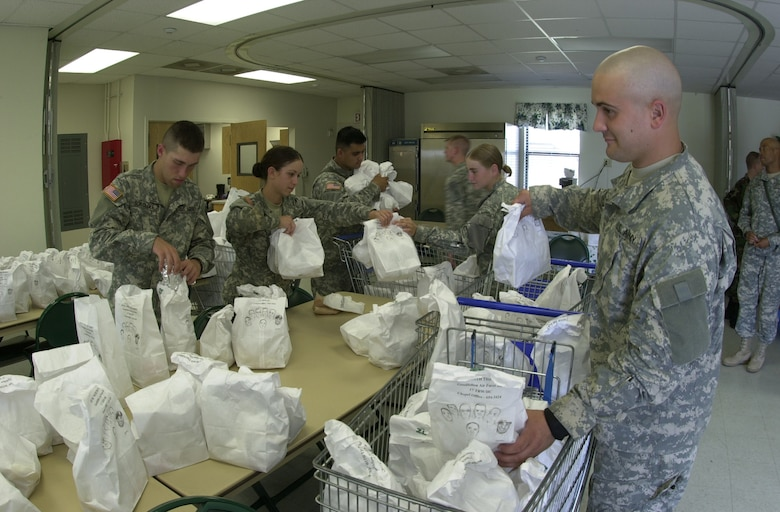 (From left to right): Army Pvts. Anson Sokoloff, Alysha Rivera, and Brian Begeal, as well as Pfc. Verna Milner and Pvt. Wesley Arnold, all student Soldiers from the  344th Military Intelligence Battalion, help put bags of food into shopping carts June 15 at the Fellowship Hall.