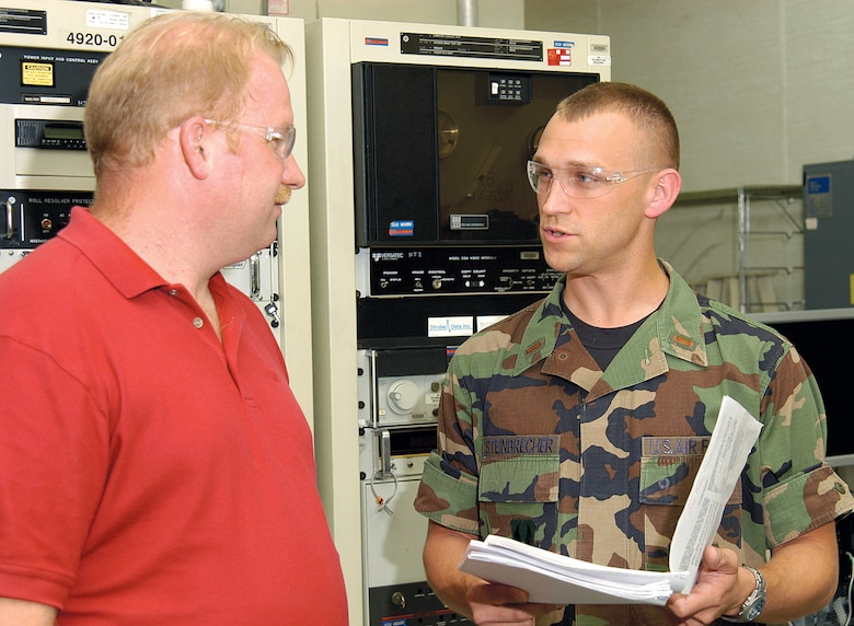 Electronics mechanic Jeff Hutchens discusses B-1 antennae work with 2nd Lt. Cory Steinbrecher recently.  As facility engineer for the B-1 Compact Range in Bldg. 3761, Lt. Steinbrecher ensures every piece of test equipment in the sole source facility is kept upgraded and in top shape. (Air Force photo Margo Wright)