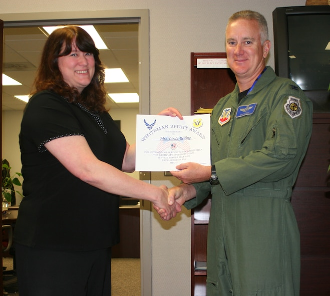 Linda Reiling, 509th Maintenance Group, receives the Whiteman Spirit Award from Col. Eric Single, 509th Bomb Wing vice commander, June 18. (U.S. Air Force photo/ Staff Sgt. Rob Hazelett)