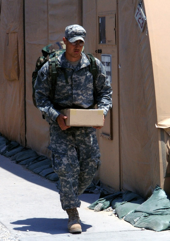Senior Airman Bradley Luu, 455th Expeditionary Communications Squadron, picks up a package from the post office after returning from a forward operating base in Afghanistan. Airman Luu travels to different forward operating bases in theater to assist with the transisition to a more efficient communications system which allows the A-10 pilots to communicate with Army ground forces for direct ground support. Airman Luu is one of many Airmen wearing the Army Combat Uniform when working alongside his Army counterparts in theater. Airman Luu is deployed from the 27th Communications Squadron, Cannon Air Force Base, N.M. (photo by Staff Sgt. Craig Seals)