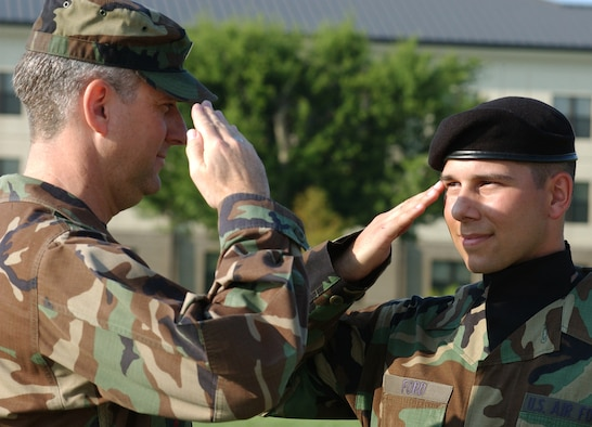 Capt. Chris Ford, left, returns a salute from his son, Airman 1st Class Chris Ford at the 81st Training Group's drill down June 15 at Keesler Air Force Base, Miss.  Airman Ford, who graduates from the basic electronic principles course July 3, follows in the footsteps of his father, who attended technical training at Keesler in 1985.  Airman Ford, 20, continues his training as an avionics electrician at Sheppard AFB, Texas.  Captain Ford, who's been at Keesler for more than three years, is the 332nd Military Training Flight commander.  He's been in the Air Force for more than 22 years and attended Officer Training School as a master sergeant after 13 1/2 years in the enlisted ranks.  (U. S. Air Force photo by Kemberly Groue)