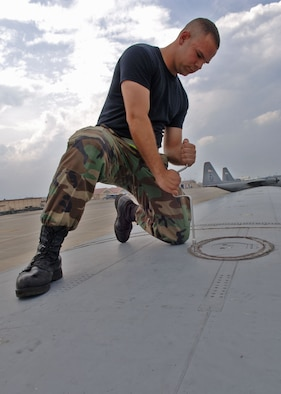 Airman Dean Atwa tightens a dry bay panel on top of a C-130 Hercules. Amn Atwa is a communication navigations and mission systems apprentice with the 374th Aircraft Maintenance Squadron.(U.S. Air Force photo by Senior Airman Veronica Pierce)