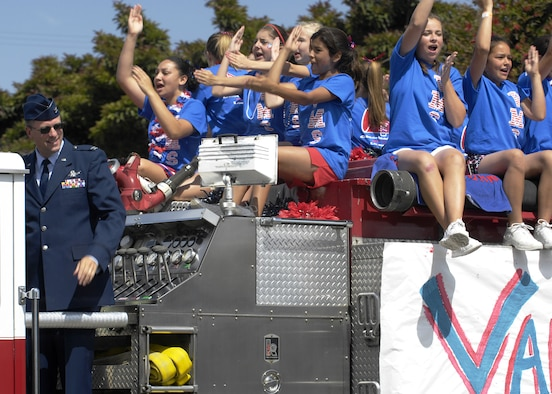 Col. Benjamin Huff, 30th Mission Support Group commander, rides on a fire engine with the Vandenberg Middle School Cheerleaders during the 55th Annual Flower Festival Parade in Lompoc on June 23.  The festival celebrated the theme of American History on Parade as bands, floats, equestrian units, drill teams, and clowns entertained the crowd. (U.S. Air Force photo/Airman 1st Class Christian Thomas)