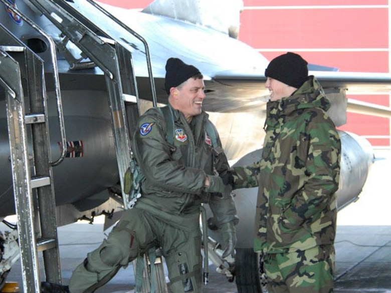 "Col. Cecil J. ""Bud"" Hensel, North Dakota Air National Guard pilot, shakes hands with his son Senior Airman Bryan M. Hensel, 119th Maintenance Squadron crew chief, after successful completion of Col. hensels's last flight in an F-16."
