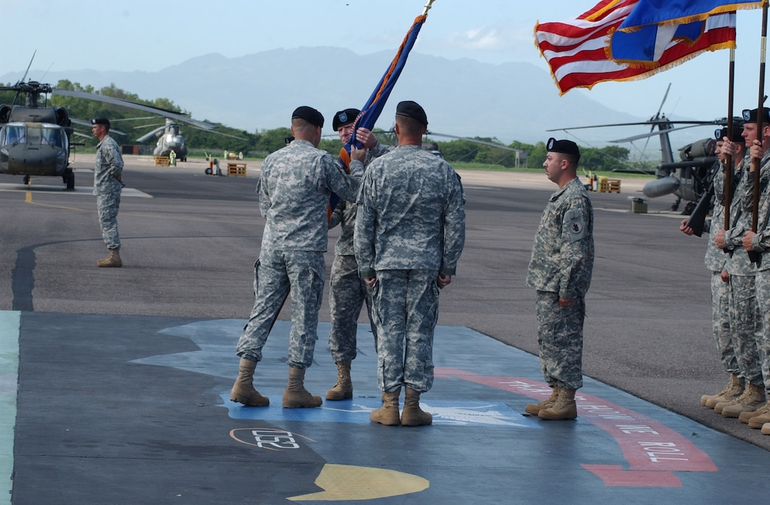 Army Lt. Col. Todd Conyers assumes command of the 1st Battalion 228th Aviation Regiment here by accepting the 1-228 AVN guidon from Brig. Gen. P.K. Keen, U.S. Army South commander, June 26 on the Soto Cano Air Base flightline. Colonel Conyers arrives from MacDill Air Force Base, Fla., where he served as an aviation maintenance and joint operations officer. U.S. Air Force photo by Martin Chahin.
