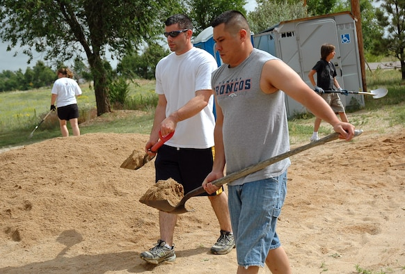 ELLICOTT, Colo. -- Staff Sgts. Joshua Avera and Daniel Bisel from the 50th Space Communications Squadron at Schriever get out their shovels as they pitch in to aid in an Ellicott Park beautification project June 27. More than 20 volunteers donated their time and elbow grease to the project. (U.S. Air Force photo/Lorna Gutierrez)