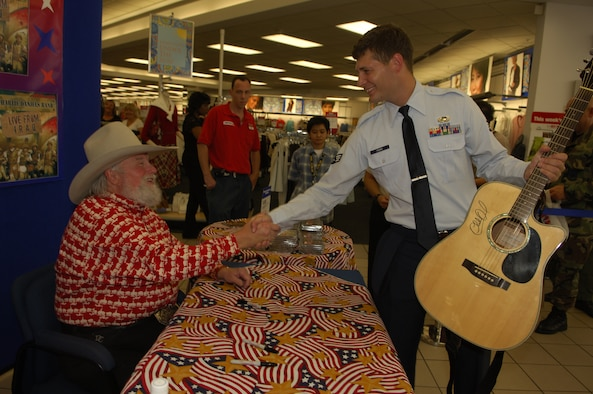 Country Western singing star Charlie Daniels shakes the hand of Senior Airman Tyler Perry, 316th Contracting Sqadron contracting specialist after signing a guitar during an event hosted by AAFES at the Base Exchange Tuesday. (U.S. Air Force photo/Tech. Sgt. Christopher Matthews)