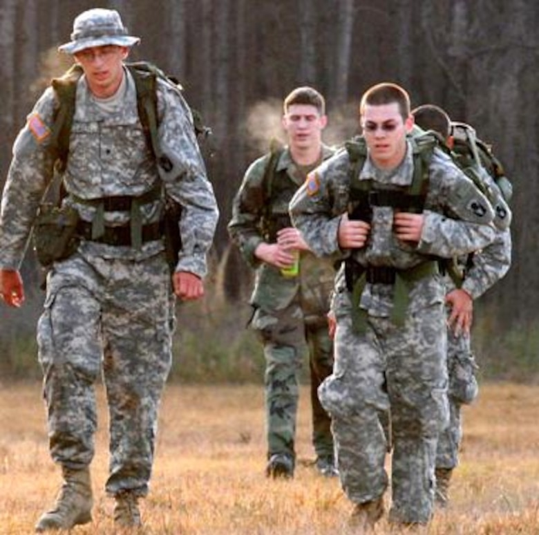Senior Amn. Williams, center, makes his way among the Soldiers during the ruck march.  He would eventually pass most of them and finish in the top two.  (Photo by Staff Sgt. Carmen Maldonaldo/FLARNG)