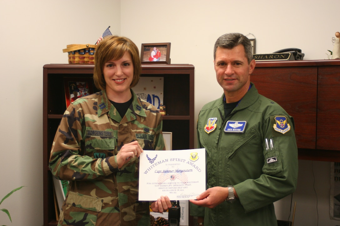 Capt. Summer Morgenstern, 509th Bomb Wing, receives the Whiteman Spirit Award from Brig. Gen. Greg Biscone, 509th Bomb Wing commander, June 4.