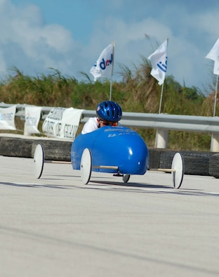 Jared with head down and leaning forward  as he is about to whiz past the finish line. The annual Guam soap box derby was held at the Yigo Racing Track. The soap box derby was sponsored by the Big Brothers/Sisters organization.