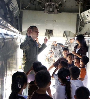 Capt. Kenneth Hills, 36th Expeditionary Bomber Squadron, shows children from Camp Freedom the inside of a B-52 June 22. Camp Freedom is a non-profit organization that helps children with deployed parents cope with their parents being gone. (Photo by Master Sgt. Art Webb, 36th EBS)