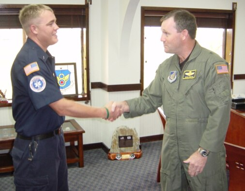 Brig. Gen. Douglas Owens, 36th Wing commander, presents William O'Meara with a coin from Michael Wynne, Secretary of the Air Force. O'Meara briefed Secretary Wynne on the fire station's confined space program. (Courtesy photo)