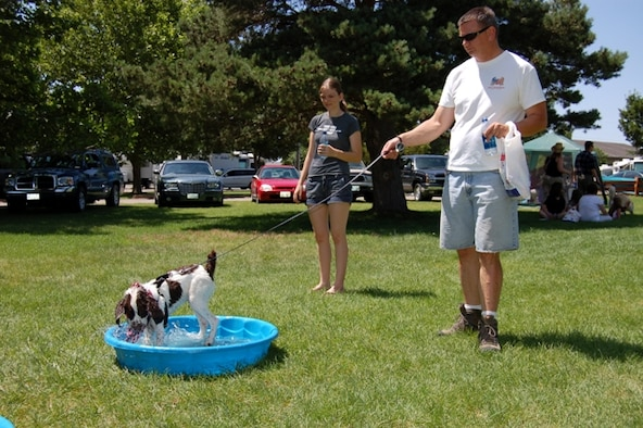 John Springer, 75th Security Forces Squadron, and his daughter, Shannon, play with their dog, Duce, in the dog splash pool at Hill AFB Bark in the Park. The event was held June 22 at Centennial Park. The yearly gathering gives families a chance to get out with their pet to do things they may not normally do, like run through an obstacle course or visit a paw reader. (U.S. Air Force photo by Senior Airman Brok McCarthy)